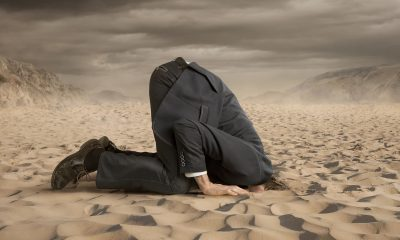 businessman hides his face on the sand