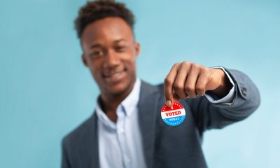 man holding voted pin