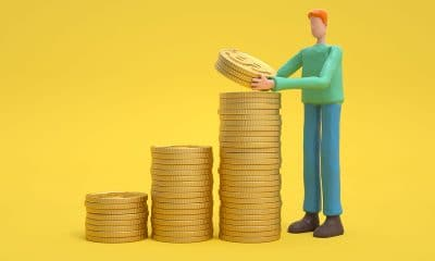 man stacking gold coins