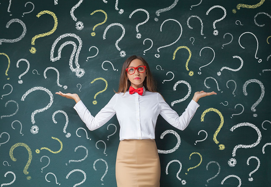 lady-standing-with-green-board-of-question-marks-behind-her