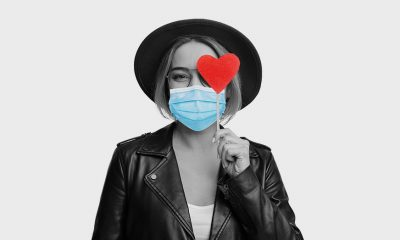 woman holding heart sticker wearing mask