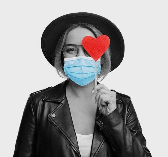 woman holding heart sticker wearing mask