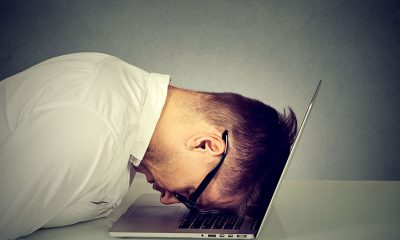 stressed man head on laptop screen