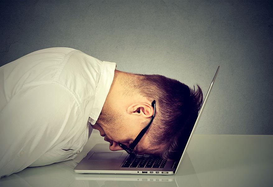 stressed man head on laptop screen