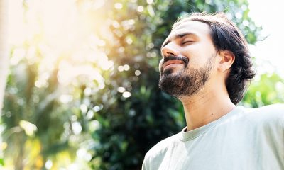 smiling man with eyes closed breathing
